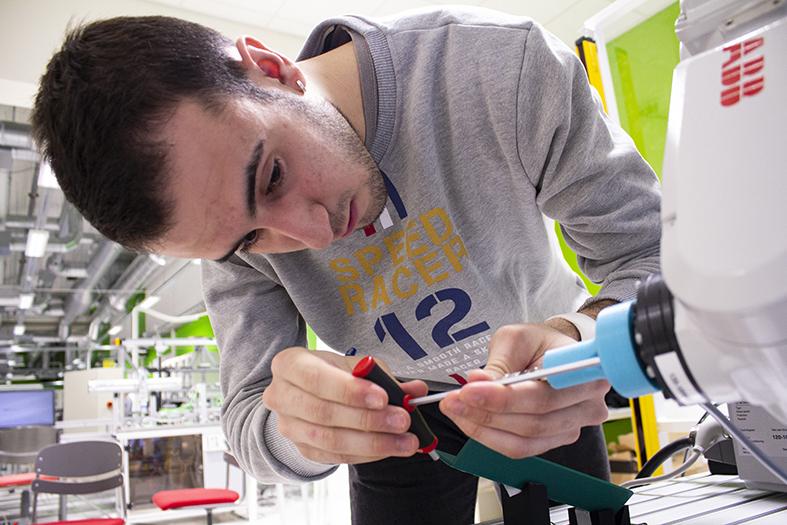 Kuvassa opiskelija Jaime korjaa robottia.