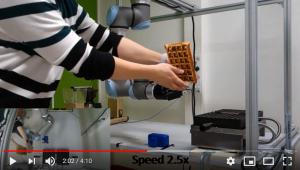Kuvassa kuvakaappaus opiskelijoiden tekemästä demovideosta, jossa robotti avustaa kahvilatyössä.