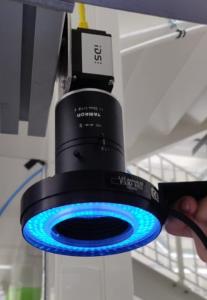 Kuvassa on konenäköjärjestelmän kamera, jonka optiikan ympärillä on ympyränmuotoinen valaisin.