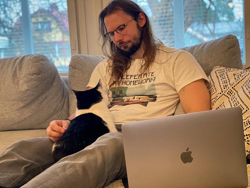 Erityisasiantuntija Aleksi Postari rapsuttelee sohvalla Vilperi-kissaansa.