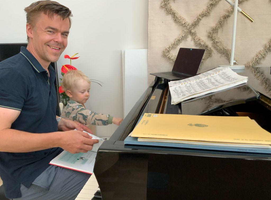 Santeri Koivisto istuu pianon ääressä poikansa kanssa.