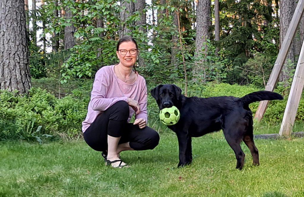 Projektitutkija Taina Jyräkoski leikkii koiran kanssa.