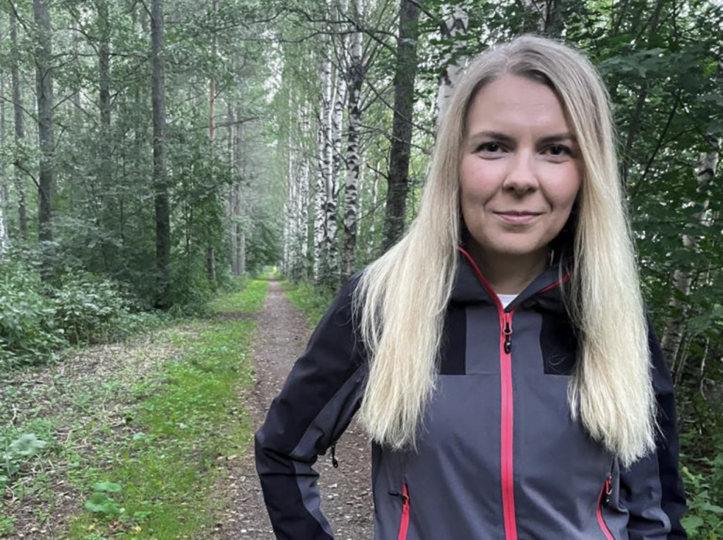 Kuvassa tutkija-opettaja Janika Tommiska vehreässä metsässä.