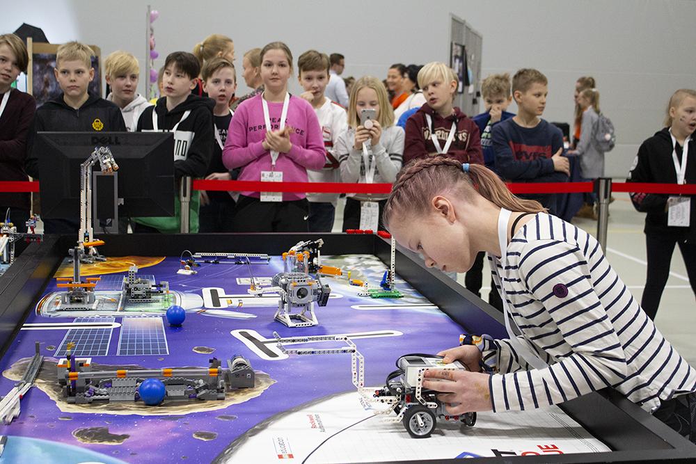 Tyttö pelaa Lego-robotilla, taustalla yleisöä.